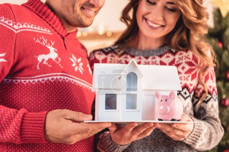 Photo for Couple in christmas sweaters holding house model and piggy bank, investment concept - Royalty Free Image