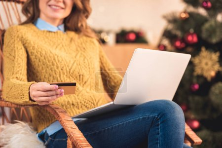 cropped view of woman shopping online with credit card and laptop at christmastime