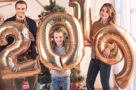 happy family with daughter holding 2019 new year golden balloons