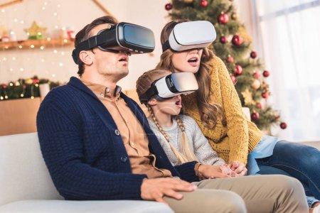 Foto de Familia sorprendido usando auriculares de realidad virtual en la casa en Navidad - Imagen libre de derechos