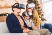 shocked family using virtual reality headsets at home at christmastime