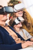 happy family using virtual reality headsets at home at christmastime