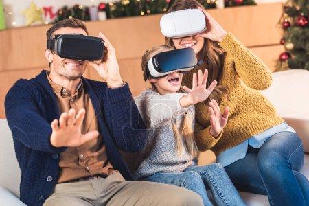 Photo pour Gestuelle familiale et à l'aide de casques de réalité virtuelle à la maison au moment de Noël - image libre de droit