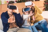 family gesturing and using virtual reality headsets at home at christmastime
