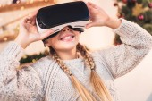 smiling female youngster using vr headset at christmastime