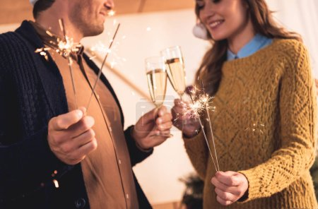 cropped view of couple celebrating new year with champagne glasses and sparklers