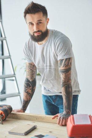Foto de Guapo hombre barbudo que se inclina en la mesa de madera y mirando a cámara durante la reparación de la casa - Imagen libre de derechos