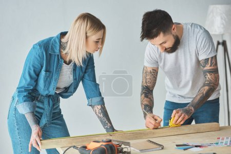 young tattooed couple working with pencil, wooden plank and measuring tape