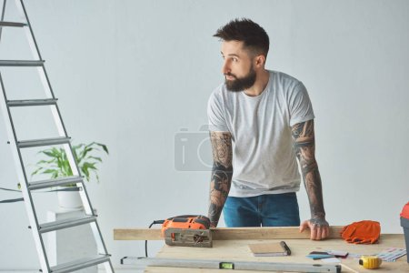 Photo for Handsome bearded man leaning at wooden table and looking away during house repair - Royalty Free Image