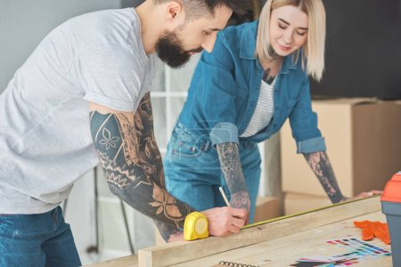 smiling young tattooed couple working with wooden plank and measuring tape
