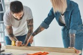 young couple working with wooden plank and measuring tape