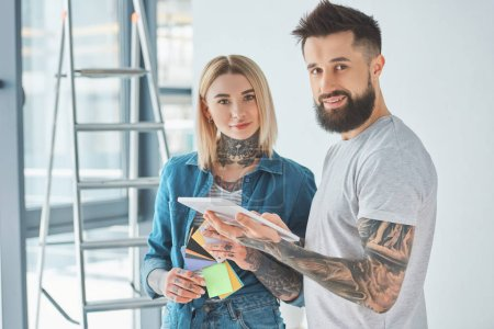 Photo for Young tattooed couple using digital tablet and smiling at camera in new home - Royalty Free Image