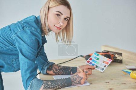 Foto de Jovencita tatuada manteniendo la paleta de colores y sonriendo a cámara en mejoras para el hogar - Imagen libre de derechos