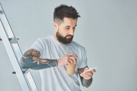 bearded young man holding paper cup and using smartphone while standing near stepladder on grey