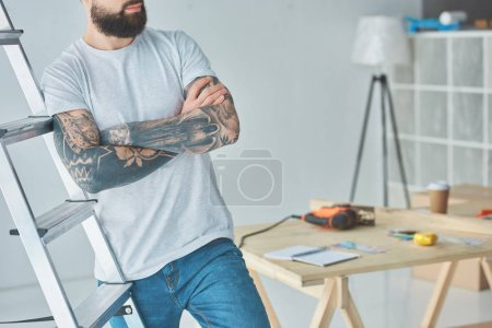 Photo for Cropped shot of bearded tattooed man standing with crossed arms near stepladder - Royalty Free Image