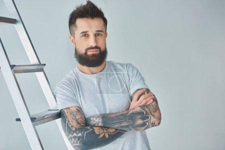 Photo pour Beau barbu tatoué jeune homme debout avec les bras croisés près d'escabeau et regardant la caméra sur fond gris - image libre de droit