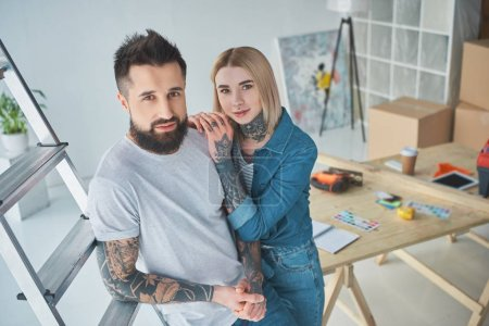 Photo for High angle view of beautiful young tattooed couple smiling at camera while standing together in new home - Royalty Free Image
