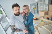 high angle view of beautiful young tattooed couple smiling at camera while standing together in new home
