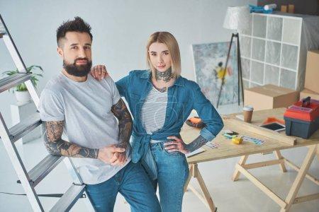 Photo pour Beau jeune couple tatoué, regardant la caméra en position debout ensemble dans la nouvelle maison - image libre de droit