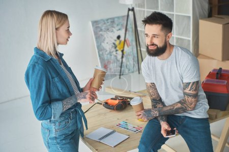 happy young couple drinking coffee from paper cups and using smartphone during home improvement