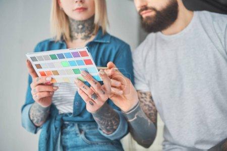 Foto de Toma recortada de joven pareja tatuada manteniendo la paleta de colores y elegir color para mejoras del hogar - Imagen libre de derechos
