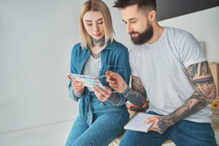 Foto de Joven pareja tatuada manteniendo la paleta de colores y elegir color para mejoras del hogar - Imagen libre de derechos