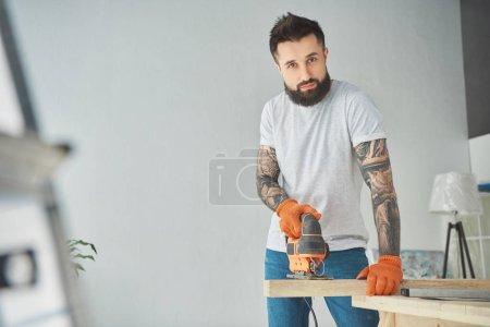 Foto de Guapo hombre barbudo tatuado con sierra mecánica para metales y mirando a cámara - Imagen libre de derechos