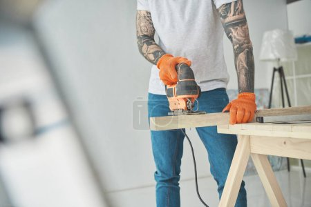 Photo for Cropped shot of young tattooed man using electric jigsaw during home improvement - Royalty Free Image
