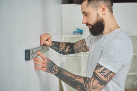 side view of handsome bearded young man holding level tool and pencil during home improvement