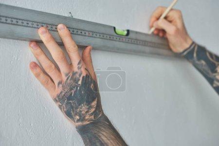 Photo pour Photo recadrée de homme tatoué tenant niveau outil et marquage mur avec un crayon pendant les réparations - image libre de droit