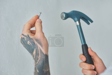 close-up partial view of tattooed young man holding hammer and nail