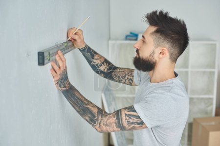 side view of tattooed young man holding level tool and marking wall with pencil during repairs