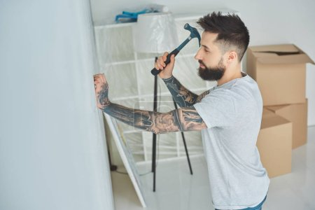 side view of bearded young man hammering nail at wall in new house