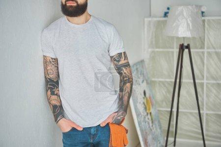 Photo pour Recadrée tir de barbu tatoué s'appuyant au mur dans Maison Neuve - image libre de droit