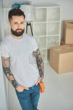 Photo for Handsome bearded tattooed man standing with hands in pockets in new house - Royalty Free Image