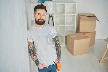 Photo pour Bel homme tatoué barbu appuyé au mur et en regardant la caméra à la nouvelle maison - image libre de droit