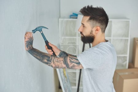 side view of bearded young man hammering nail at wall