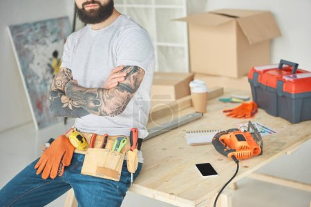 cropped shot of bearded tattooed man with tool belt sitting with crossed arms on wooden table