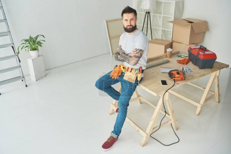Photo for High angle view of handsome bearded tattooed man with tool belt sitting with crossed arms and looking at camera - Royalty Free Image