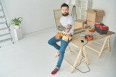 high angle view of handsome bearded tattooed man with tool belt sitting with crossed arms and looking at camera