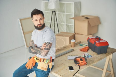 Photo for Handsome bearded man with tool belt sitting with crossed arms and looking at camera - Royalty Free Image