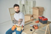 handsome bearded man with tool belt sitting with crossed arms and looking at camera