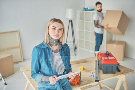 Photo for Girl holding digital tablet and looking at camera while boyfriend holding cardboard box behind - Royalty Free Image