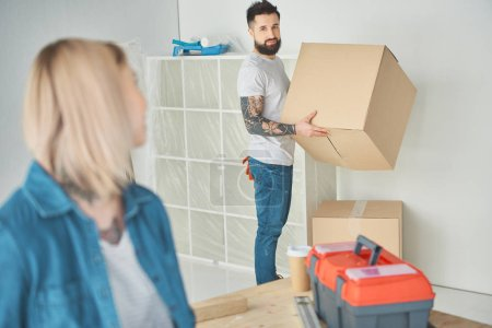 young woman looking at bearded boyfriend holding cardboard box in new house