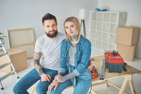 Photo for Happy young couple in tattoos sitting together and smiling at camera while making repairs in new house - Royalty Free Image