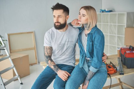 Photo for Young couple with tattoos sitting together and looking away in new home - Royalty Free Image