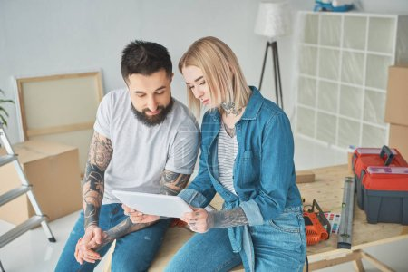 Photo for Beautiful young couple using digital tablet during home improvement - Royalty Free Image