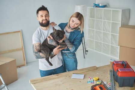happy young couple playing with french bulldog during home improvement