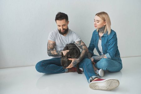 Photo for Happy young couple sitting and playing with french bulldog on grey - Royalty Free Image