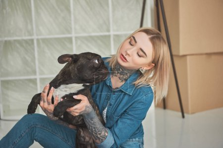 beautiful tattooed girl playing with french bulldog in new home